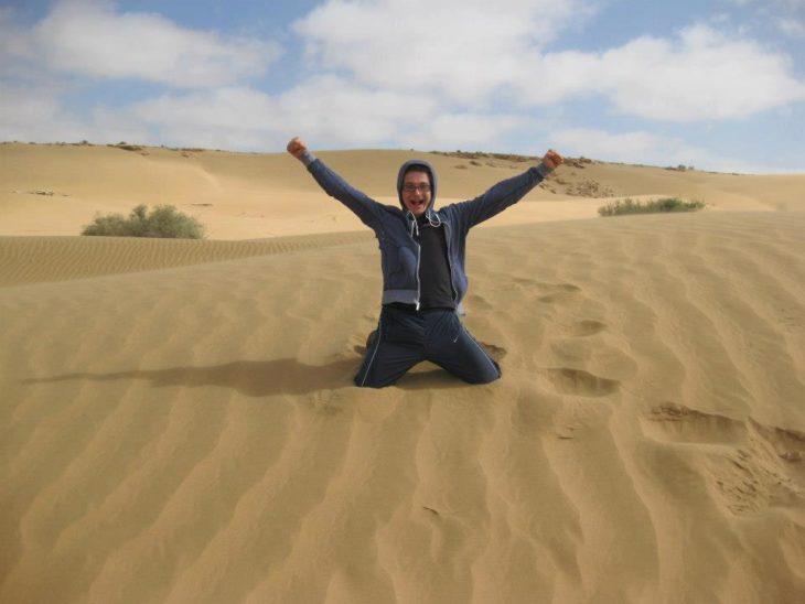 chico incado sobre el desierto de el Sahara
