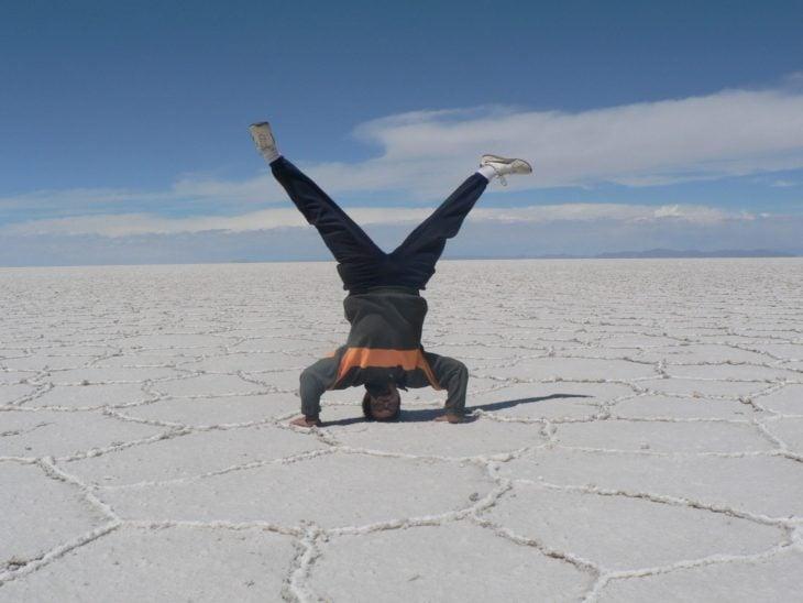 chico parado de cabeza sobre el salar en Bolivia