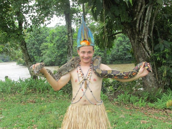 chico con una enorme serpiente en la selva del amazonas