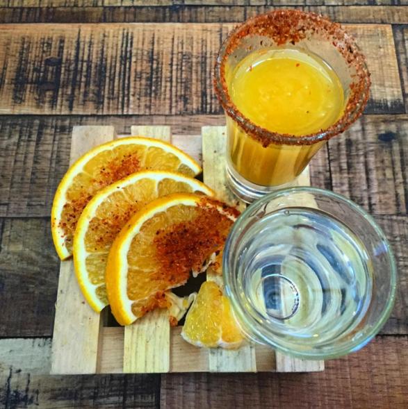 vaso de vidrio con mezcal chile y naranja