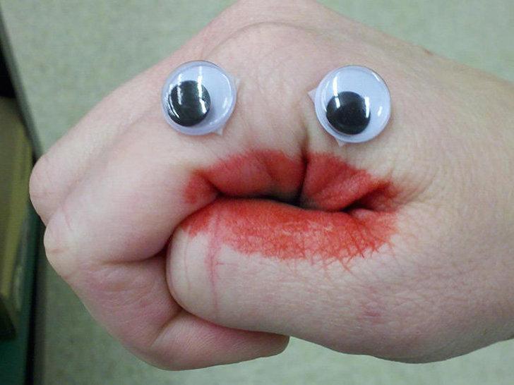 mano de una persona con ojos de plástico