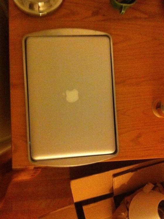 Mcbook dentro de una bandeja sobre una mesa de madera