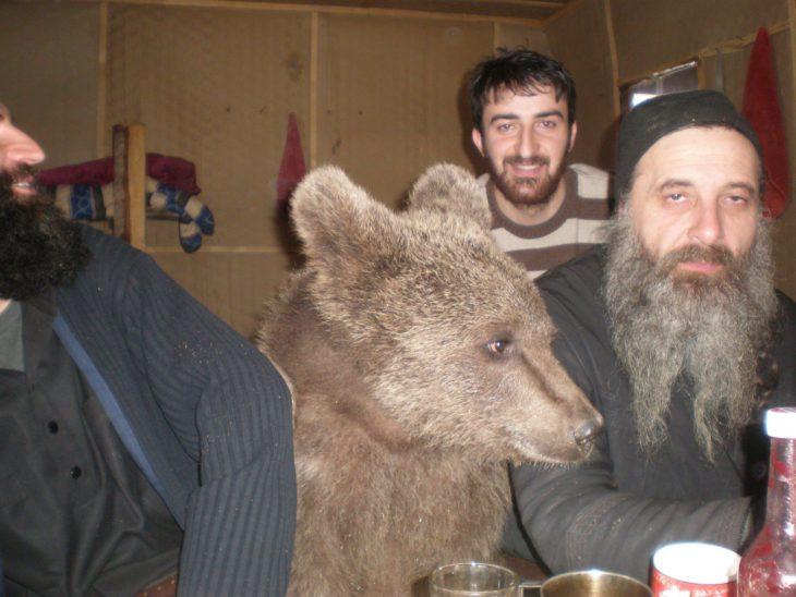 foto de unas personas sentadas rodeando a un pequeño oso