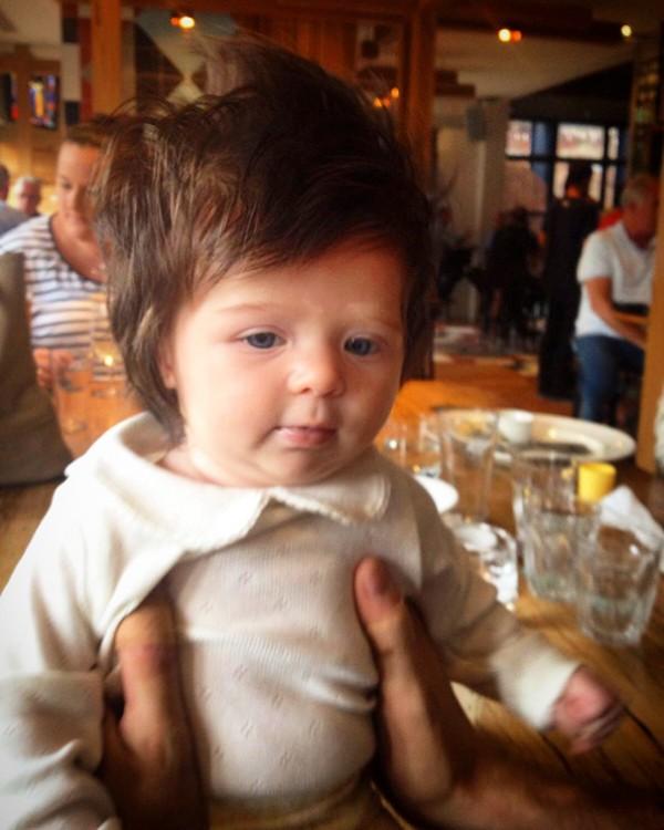 foto de una niña con mucho cabello sentada sobre la mesa de un bar