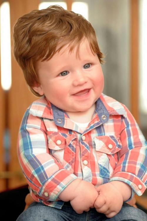Foto de un bebé sentado con el cabello pelirrojo