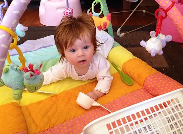 imagen de una bebé pelirroja con mucho cabello acostada sobre una cobija