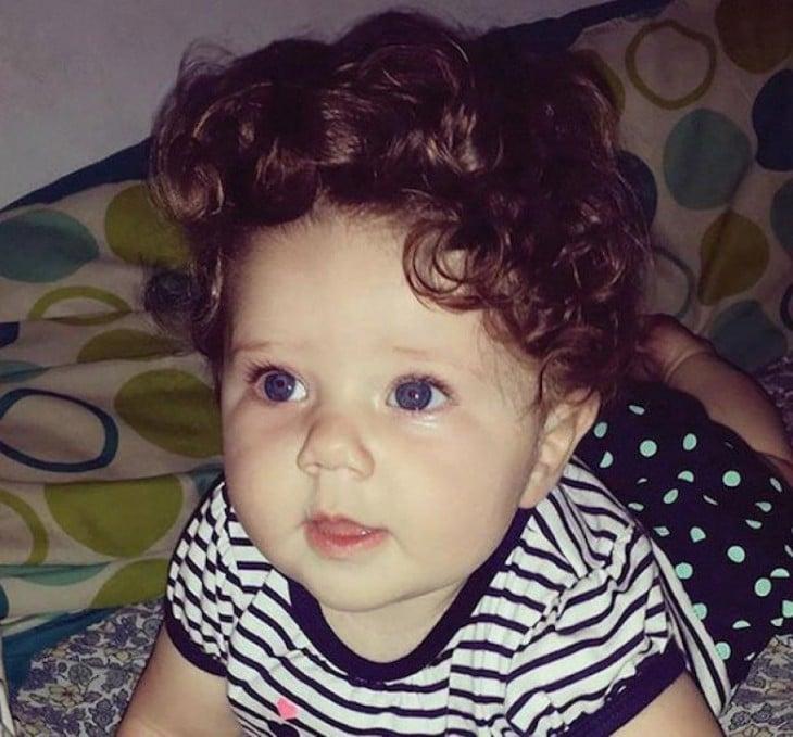 fotografía de una bebe con mucho cabello chino acostada sobre una cama