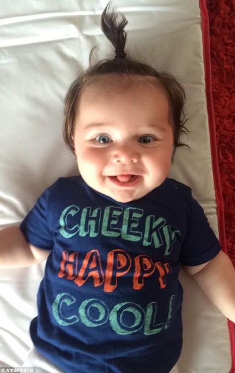 foto de una bebé acostada en una cama con una colita en su cabello