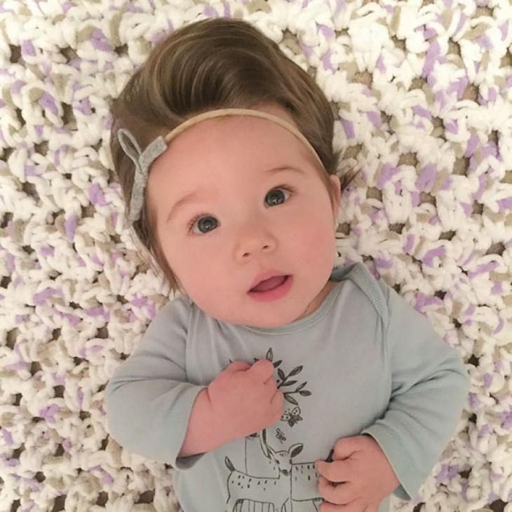 fotografía de una bebé acostada con una diadema en su cabello