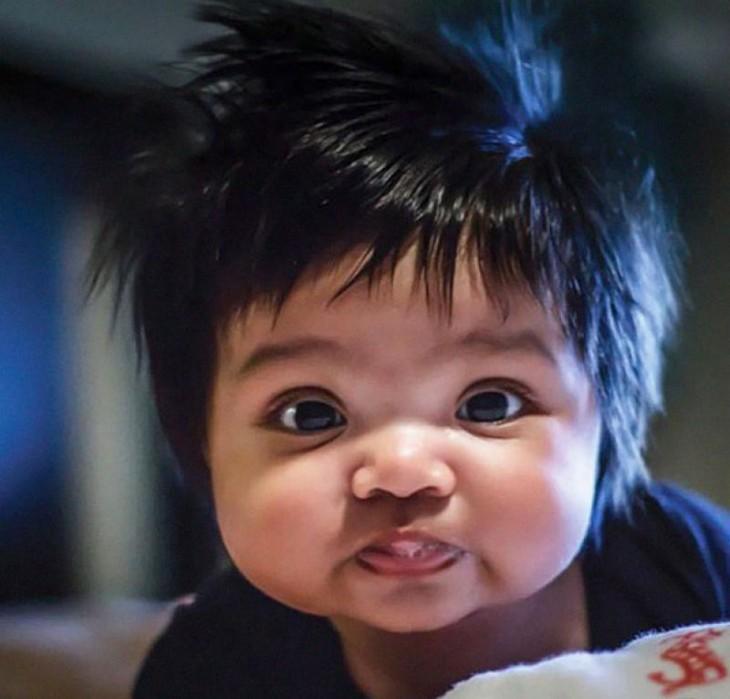 imagen de un bebé con mucho cabello y saliva en su boca