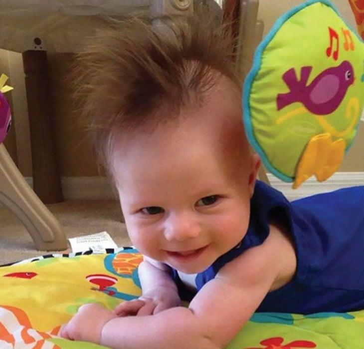 foto de un niño boca abajo con una moja de un cabello muy largo