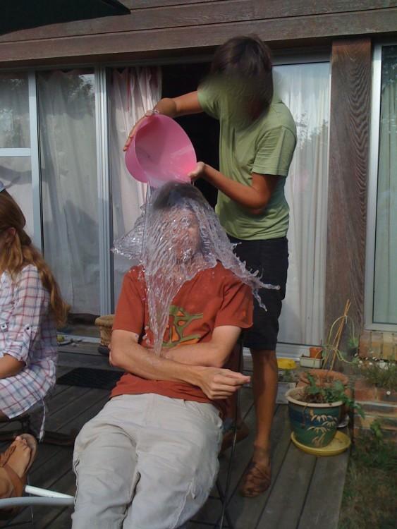 foto justo antes de que una mujer vacie una cubeta de agua sobre un chico