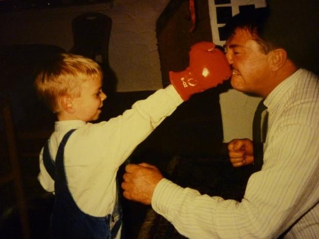 foto de un niño golpeando a su papá con un guante de box