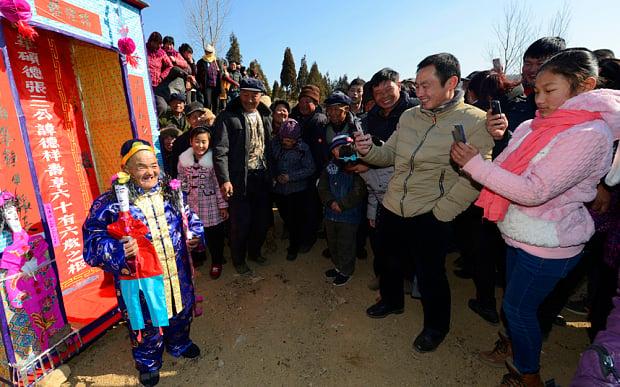 Hombre chino que fingió su muerte posando ante los celulares de varios aldeanos asistentes