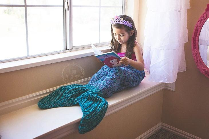 Cola de sirena con una niña leyendo en la ventana