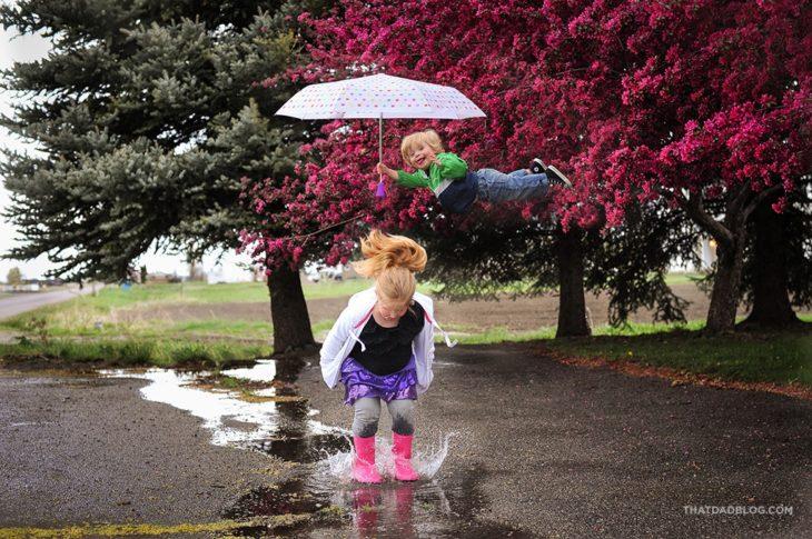William, el niño con Síndrome de Down que puede volar, sosteniendo un paraguas arriba de su hermana mientras ésta brinca en un charco