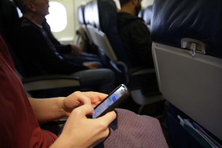 mujer sentada en un avión mensajeando con un celular