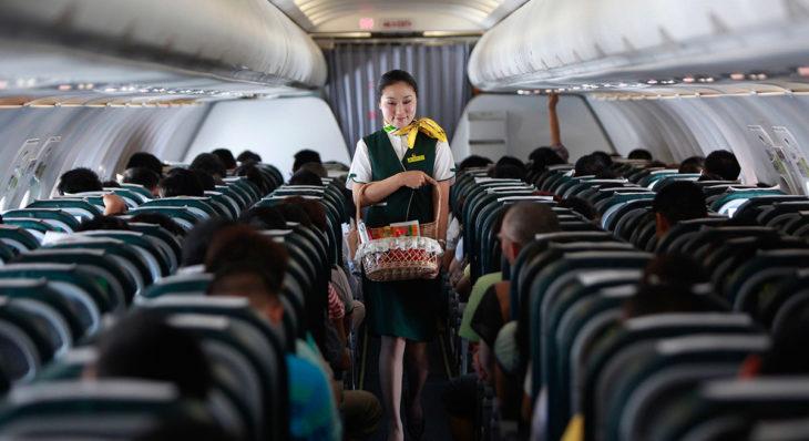 aeromosa caminando por el pasillo de un avión