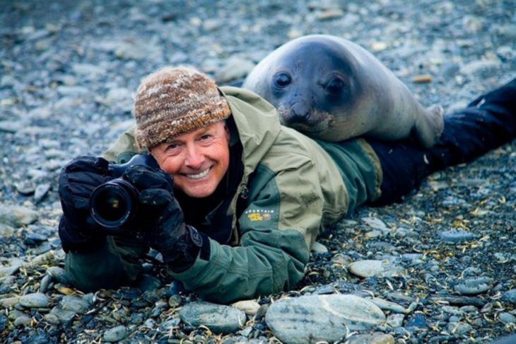 una foca se acuesta encima de un fotógrafo