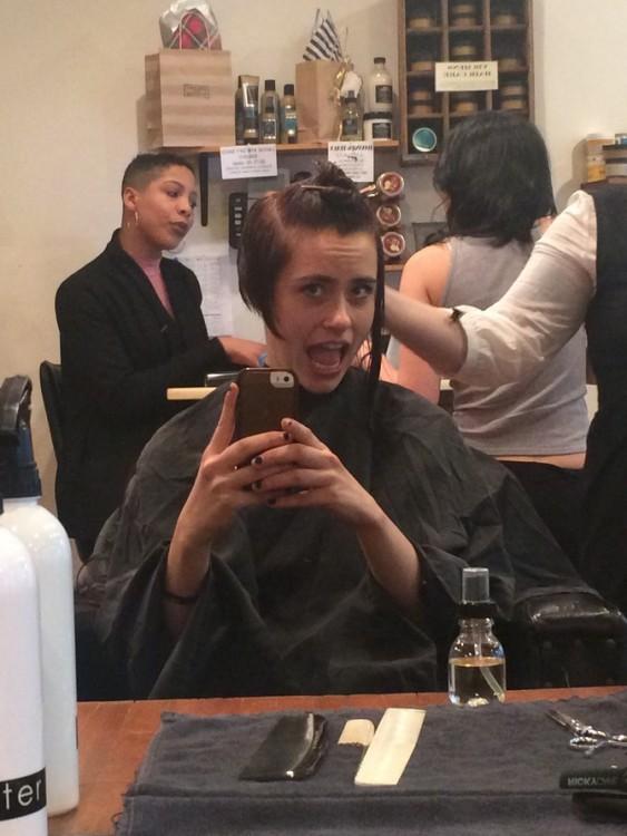 mujer tomándose foto mientras le cortan el cabello