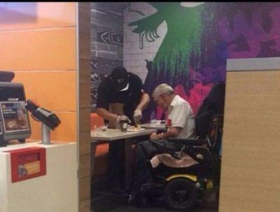 empleado ayuda a hombre discapacitado a cortar su comida