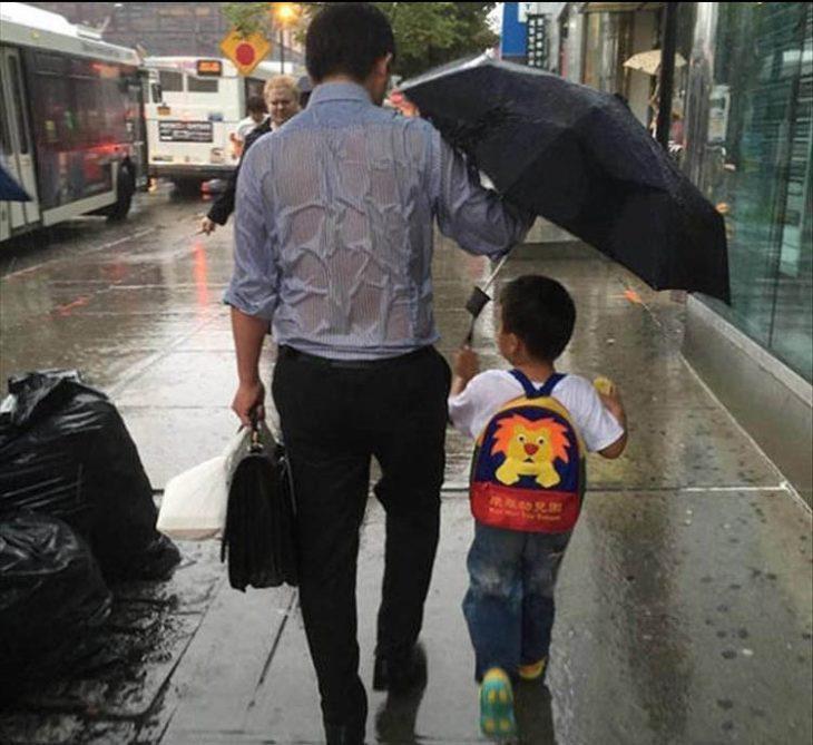 papá e hijo caminando en la lluvia y el papá va empapado pero el niño lleva el paraguas