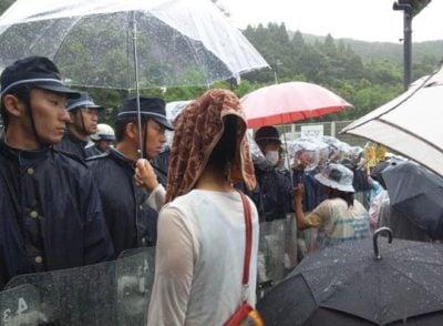 manifestantes comparten sus paraguas con oficiales