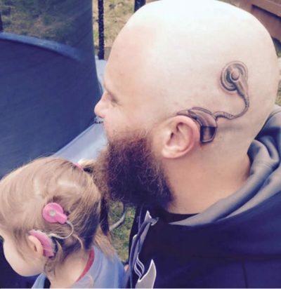 papá con un tatuaje de un aparato auditivo junto a su hija con un aparato auditivo
