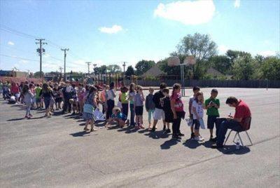 niños hacen fila para que el conserje de su escuela les firme su anuario