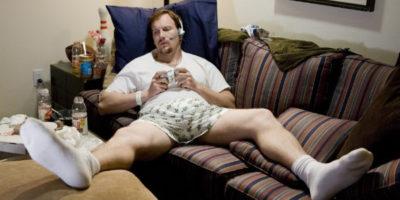Hombres no maduramos. Hombre tirado en el sofá en calzones jugando video juegos