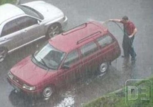 Hombre lava su carro en medio de un aguacero