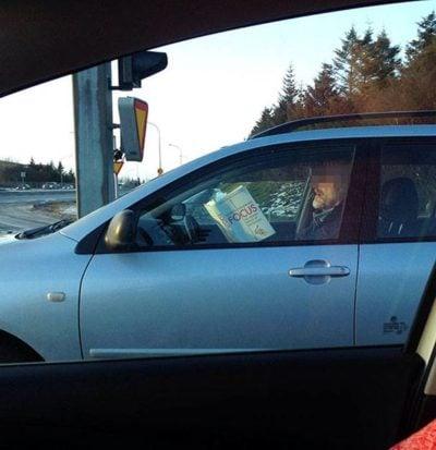Ironía, un hombre lee un libro que se llama CONCÉNTRATE mientras maneja