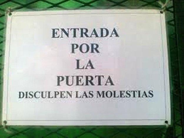 Ironía, letrero en donde dicen que la entrada es por la puerta