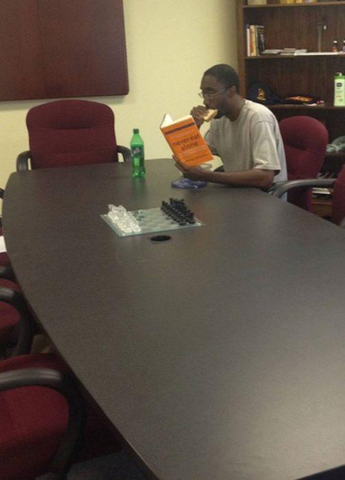 Ironía, hombre leyendo un libro de cómo nunca comer solo mientras come solo