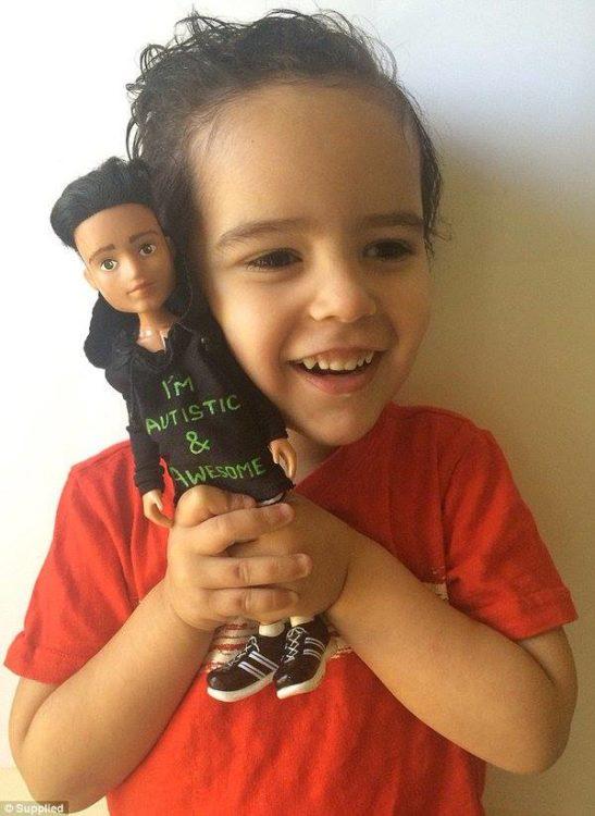 Niño con autismo con un muñeco que trae una playera que dice que tiene autismo #ToyLikeMe
