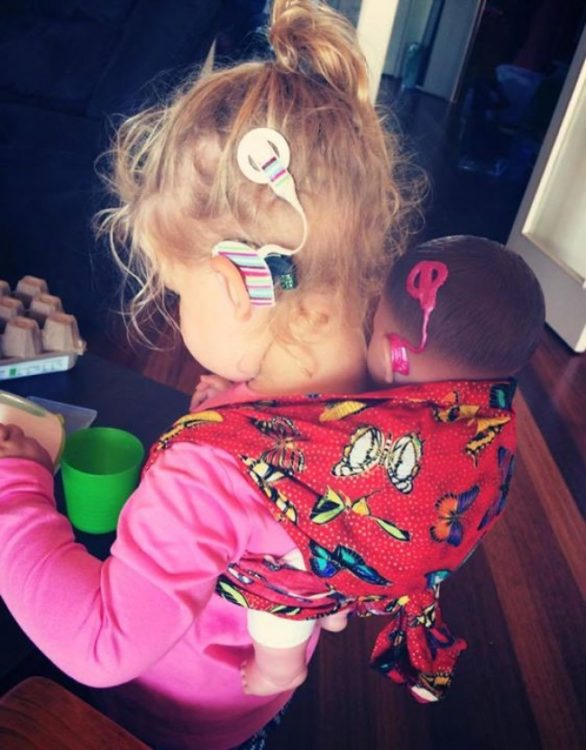 Niña usando un aparato auditivo y con su muñeca que tiene también un aparato auditivo #ToyLikeMe