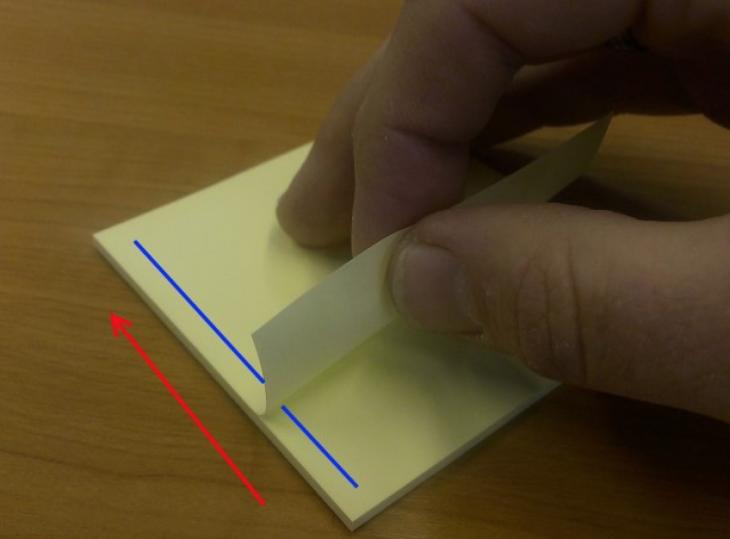 alguien separando post it de bloque con el pegamento del lado izquierdo