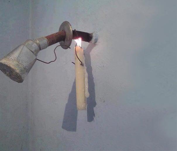 vela prendida en regadera para calentar el agua