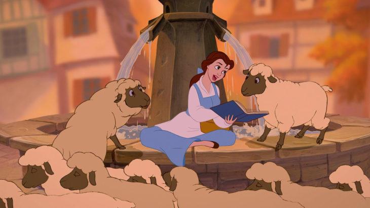 escena de Bella leyendo un libro rodeada de ovejas