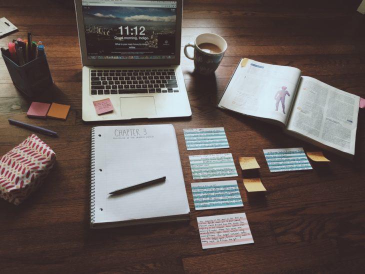 Escritorios organizados e inspiradores. Escritorio de madera con libreta, notas, post its y plumones y laptop y café