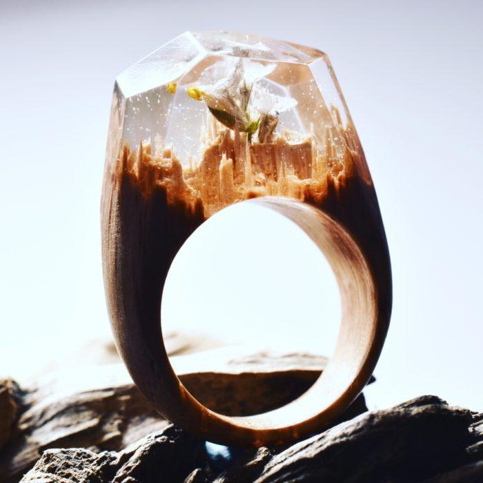 anillo de madera con un minipaisaje y una flor encapsulado en su interior