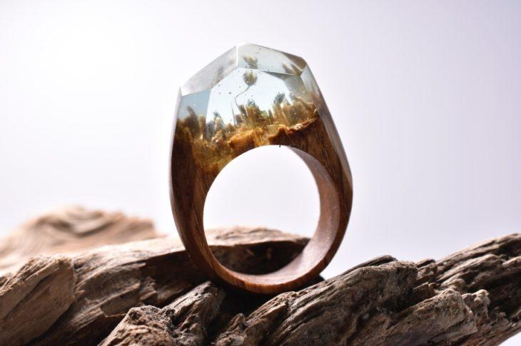 anillo de madera con un minipaisaje dentro y una flor en color blanco