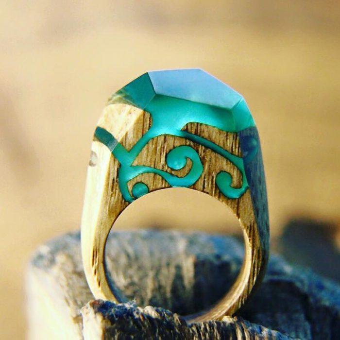 anillo de madera con tallados en su madera encapsulado en resina color turquesa