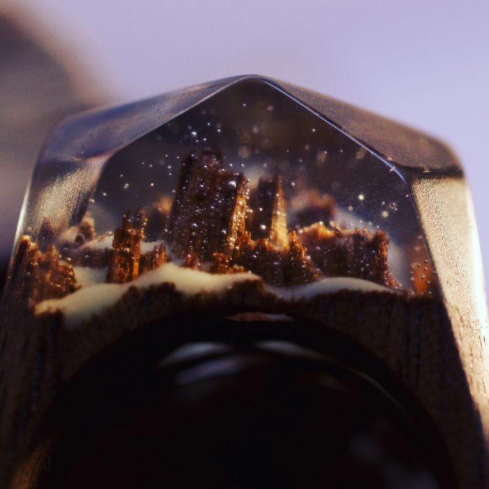 minipaisaje nocturno de edificios encapsulado dentro de un anillo de madera