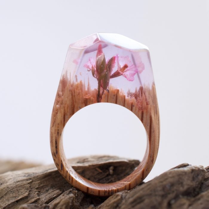 anillo de madera con una flor rosa dentro
