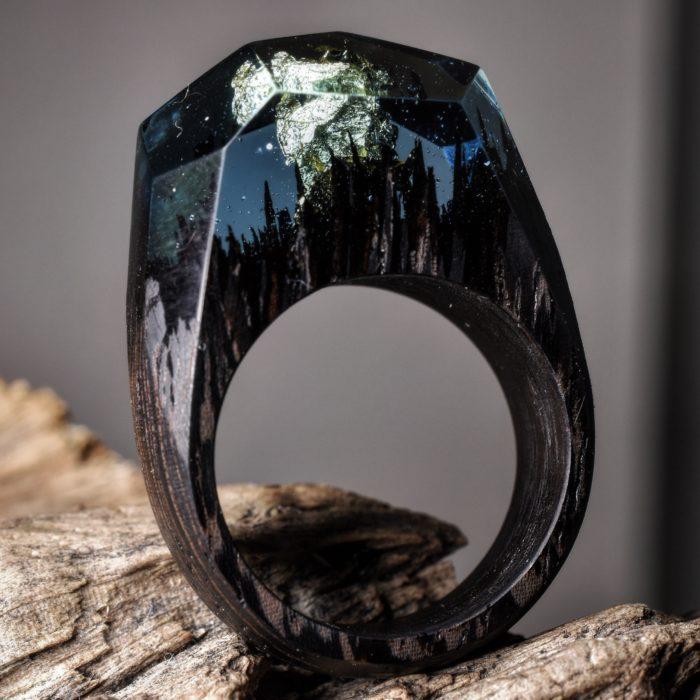 anillo de madera con un paisaje oscuro lleno de montañas y árboles