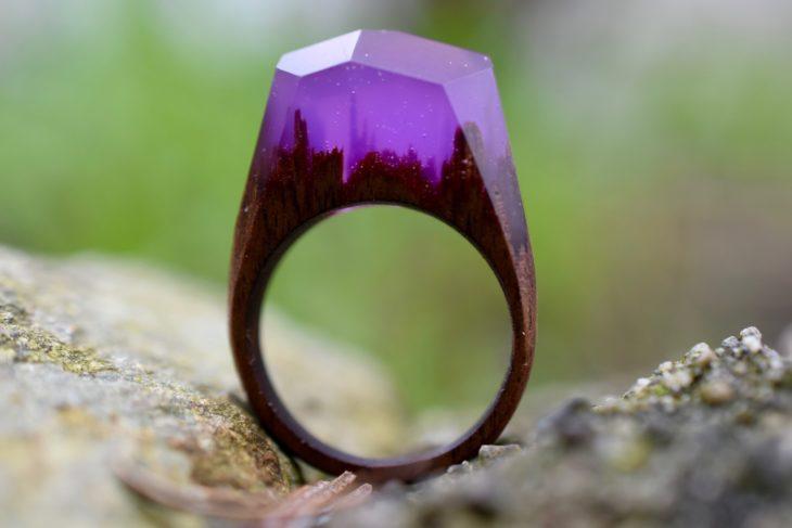 anillo de madera con un paisaje encapsulado con un material de cristal en color morado