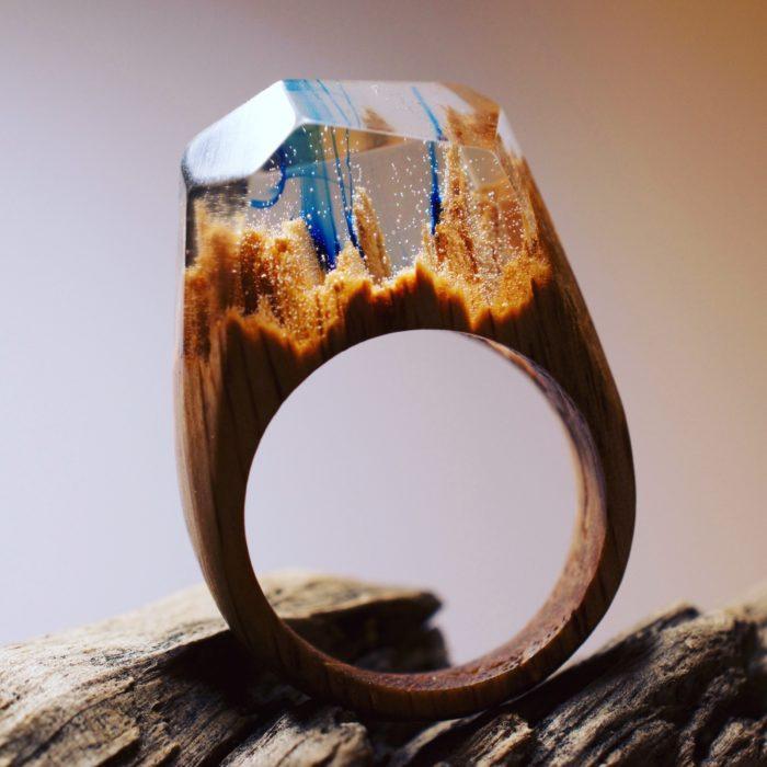 anillo de madera con un paisaje de árboles con un poco de tinta azul