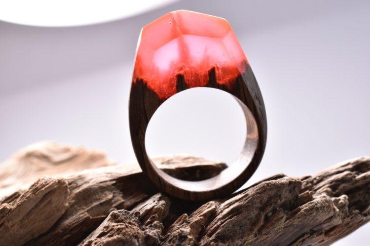 anillo de madera encapsulado en resina en color rojo con un minipaisaje dentro