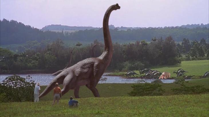 escena de un enorme dinosaurio con la mano de un bebé señalando